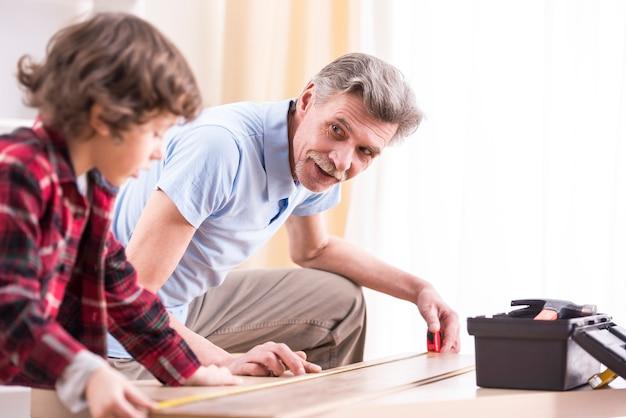 祖父と孫はテーブルを測定しています。