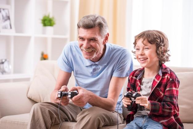祖父と孫が家でビデオゲームをしています。