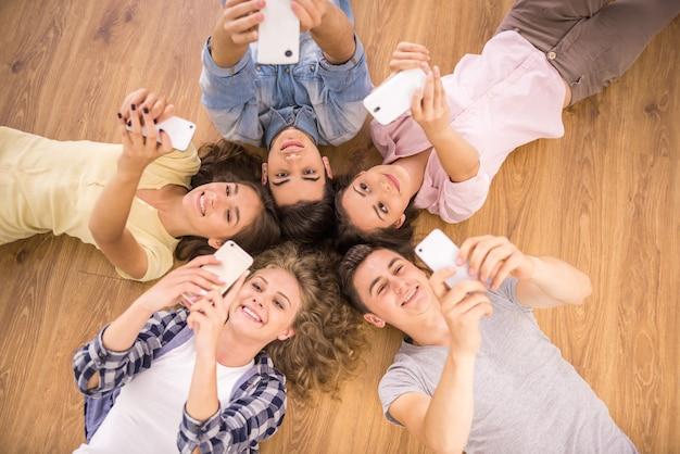 Друзья с смартфонов, лежа на полу в кругу.