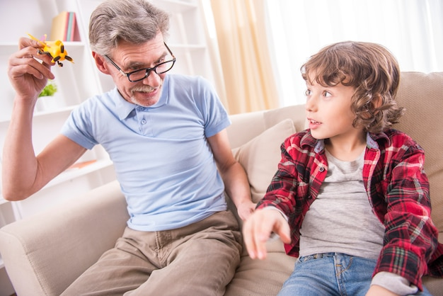 幼児男の子と彼のおじいちゃんは飛行機のおもちゃで遊んでいます。