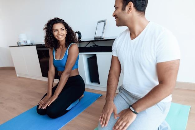 Афро американская пара делает упражнения йоги на ковер