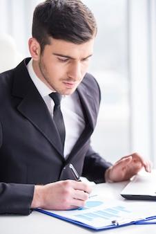 集中しているビジネスマンは彼のオフィスでグラフを分析しています。