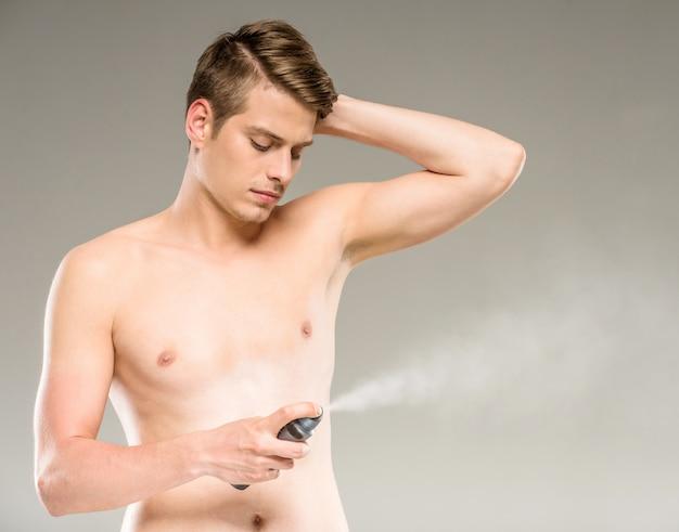 脇の下に消臭剤を適用する若いハンサムな男。
