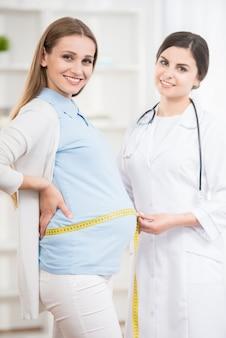 医者は彼女の妊娠中の患者の診療所のおなかを測定します。