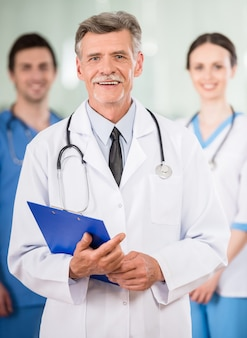 Опытный врач с молодыми коллегами в кабинете врача.