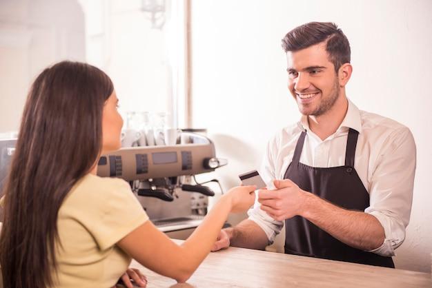 女性はクレジットカードでコーヒーを払っています。