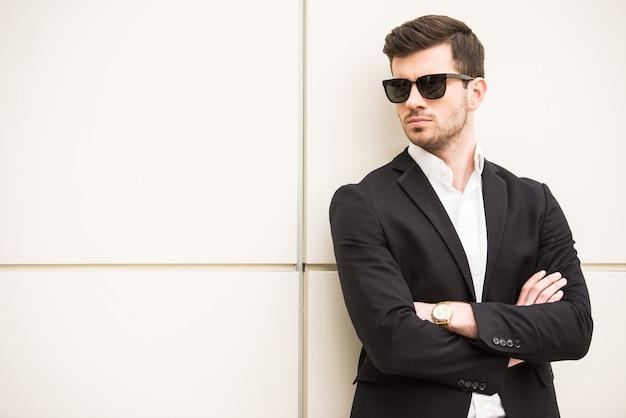 黒い眼鏡をかけた男が壁の前でポーズします。