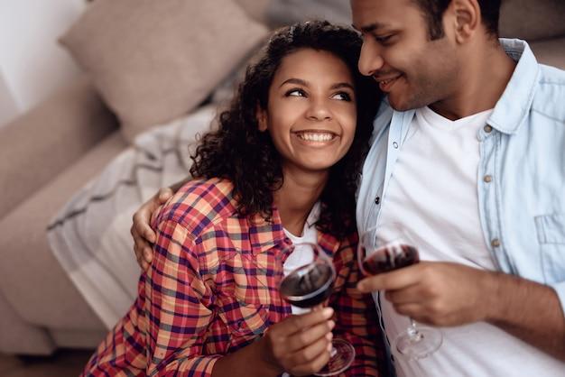 アフロアメリカンのカップルはロマンチックな日にワインを飲みます