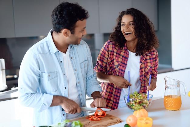 アフロアメリカンのカップルがキッチンでサラダを調理