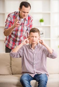 父親が彼を叱っている間、息子は耳を閉じていました。