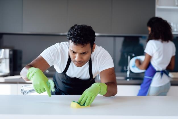 アフロアメリカンのカップルが台所の掃除