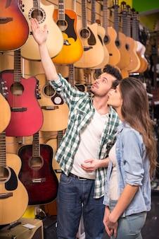 男は音楽店で女の子のギターを見せています。