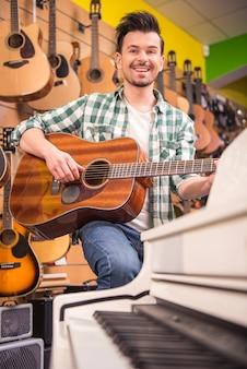 Человек играет на гитаре в музыкальном магазине.