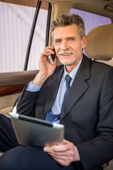 電話で話している成熟したハンサムな実業家。