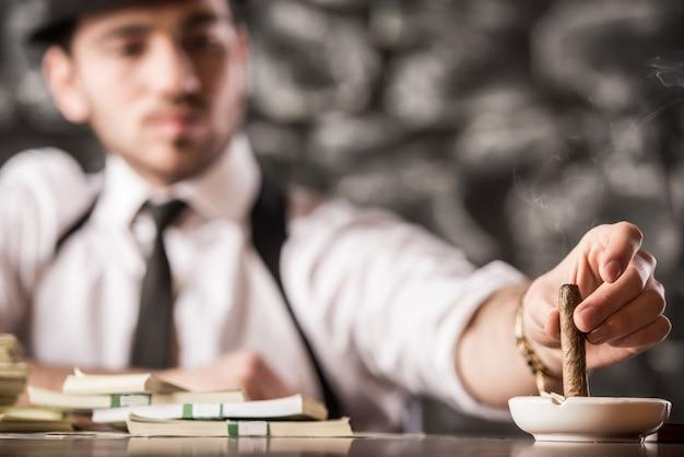 Уверенный гангстер человек курит кубинскую сигару.