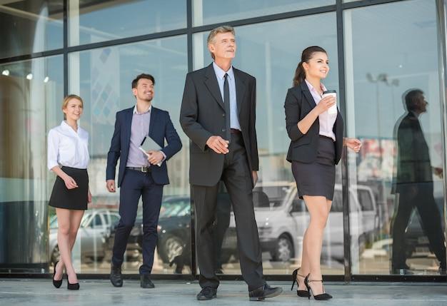Успешные деловые люди в костюмах движутся вперед вместе.