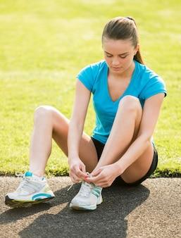 Привлекательная спортивная девушка сидит на дороге и завязывает шнурки