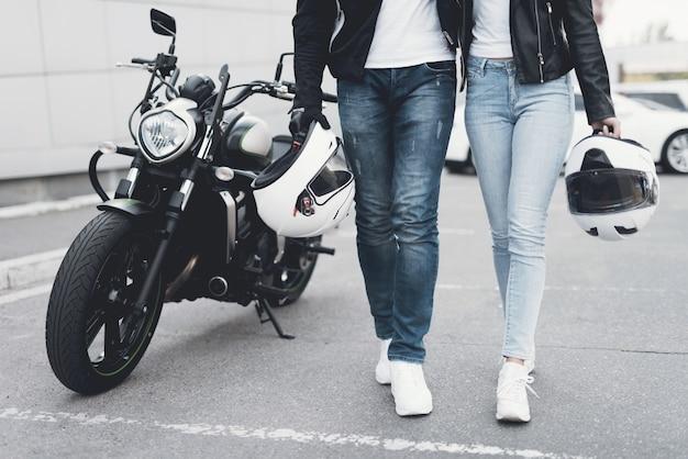 オートバイから離れて歩く若いカップル