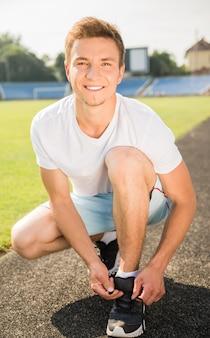 Молодой спортивный человек сидит на дороге и завязывает шнурки.