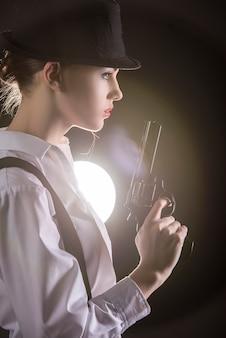 銃を保持している若い女性のギャング。
