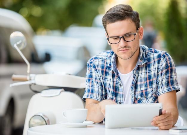 男は歩道のカフェに座っている間デジタルタブレットを使用しています。