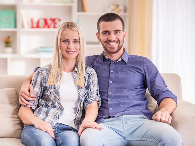 自宅でソファに座っている若いカップルを愛する。