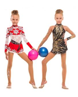 美しい双子の女の子がボールでポーズをとっています。