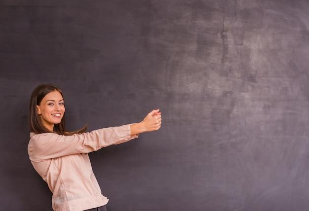 女の子は灰色の背景の上に立ち、手をスペースに引っ張ります。