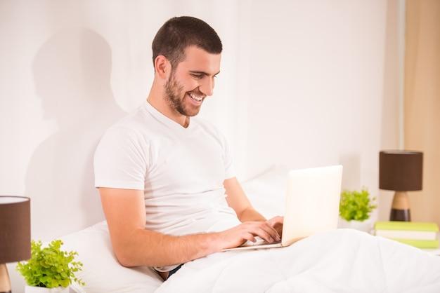 若者が自宅のベッドで横になっているラップトップを使用して