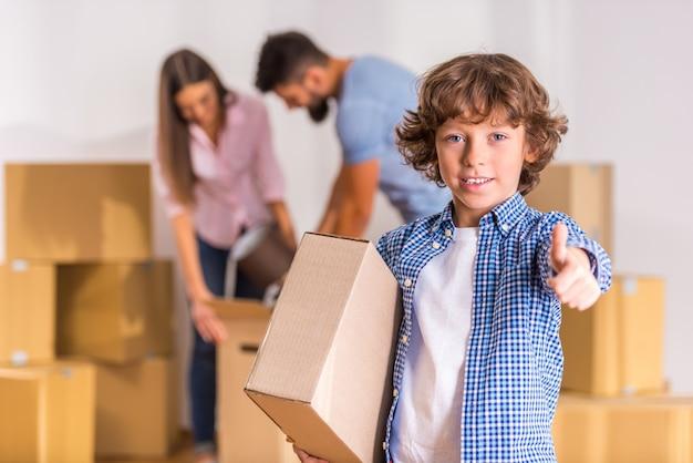 小さな男の子は箱と一緒に立ってカメラに見えます。