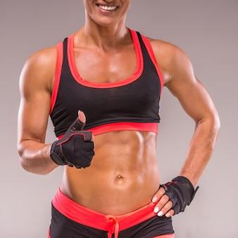 美しい筋肉ボディービルダーの女性は親指を現しています。