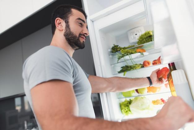 スポーティな男は冷蔵庫から野菜を取ります。