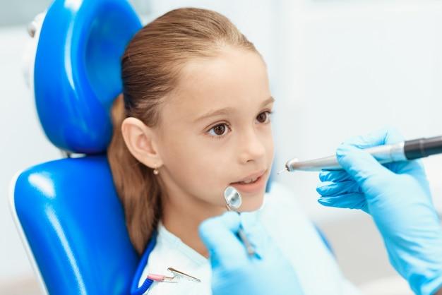 歯医者は少女の歯を調べます。歯の健康管理。