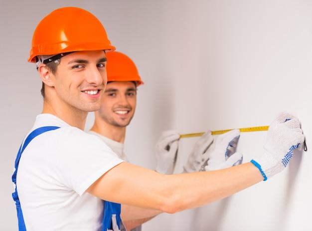 Двое мужчин в казаках делают ремонт в новой квартире.
