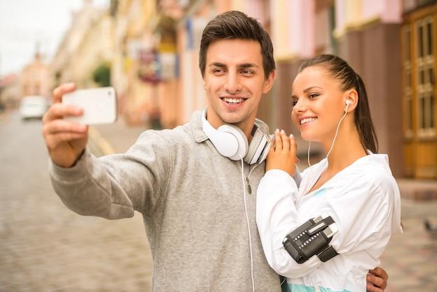 Молодые люди в спортивной одежде делают фото селфи.