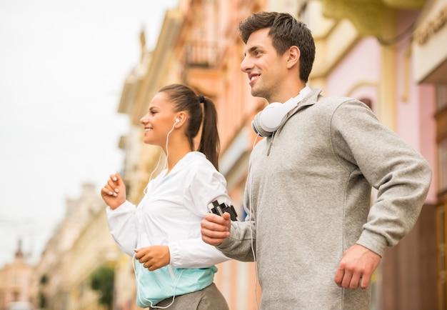 屋外で走っている若い幸せなカップル。