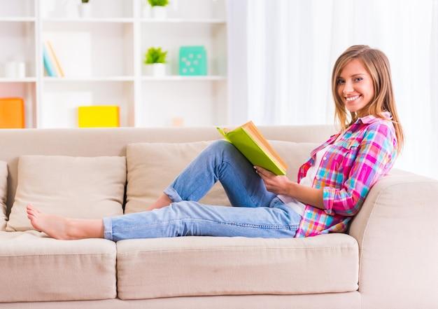 家でソファに座って本を読む女。