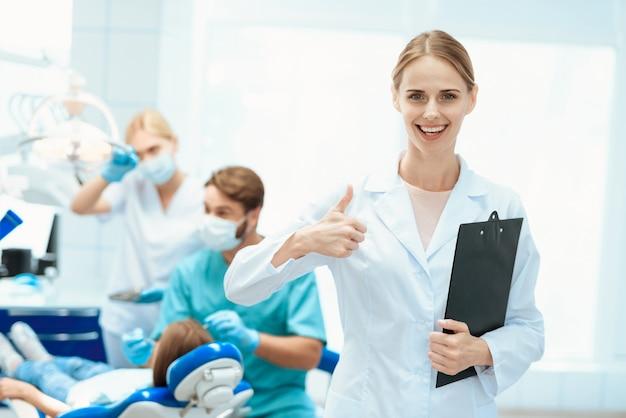 看護師の親指に対してポーズ。歯科医院。