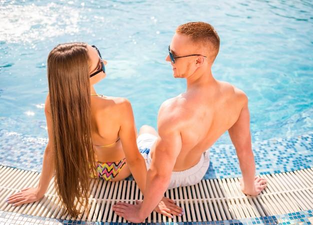スイミングプールで若いカップルの背面図です。