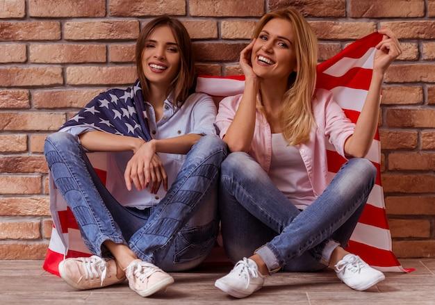 Девушки улыбаются и держат американский флаг.