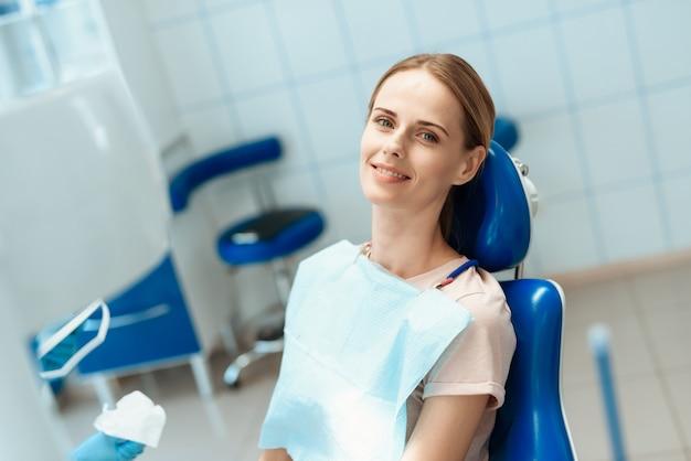女性が青い歯科用椅子でポーズをとると笑みを浮かべて