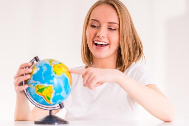 Портрет молодой женщины выбирает место на земном шаре.