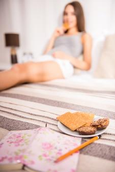 Молодая женщина сидит на кровати у себя дома.