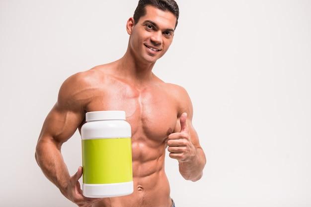 Улыбается мускулистый мужчина с банкой белка.
