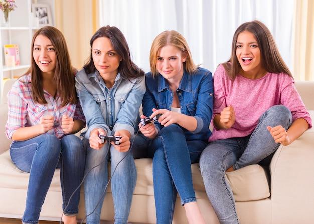 Группа молодых девушек, сидя на диване у себя дома.
