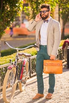 シティバイクひげを持つ若者、自転車で街を歩く