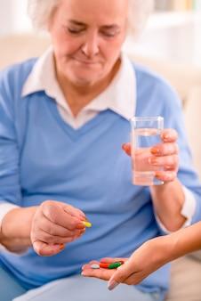年配の女性はコップ一杯の水を保持しているとピルを飲みます。