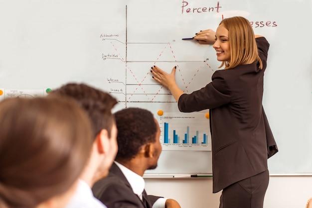 ビジネススーツの女の子は同僚に何かを伝えます。