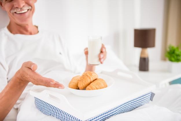幸せな先輩男がベッドで朝食をとります。