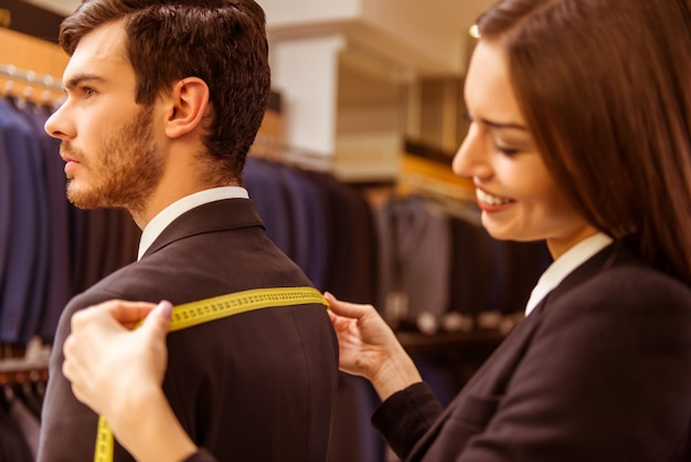 少女は男性の肩の寸法を測ります。